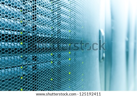 Abstract of modern high tech internet data center room with rows of racks with network and server hardware. - stock photo