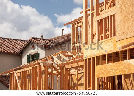 Abstract of New Home Construction Framing And Completed House. - stock photo