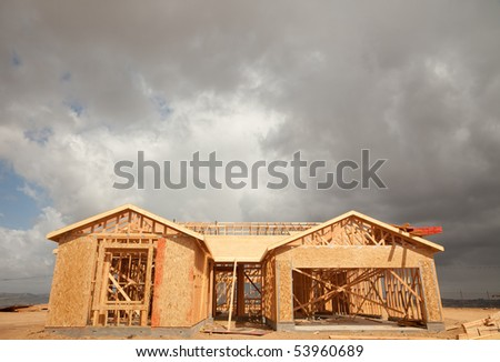 Abstract of New Home Construction Site Framing and Dramatic Clouds Overhead. - stock photo