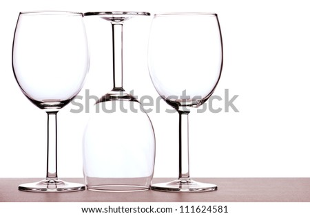 Abstract of three empty wine glasses backlit against white background. - stock photo