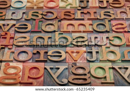 abstract of vintage wooden letterpress printing blocks stained by color inks, placed in a random order, selective focus - stock photo