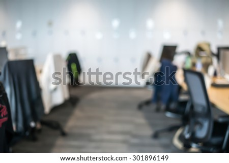 Abstract office blur background with wooden desk, chair with laptop/pc and display - stock photo
