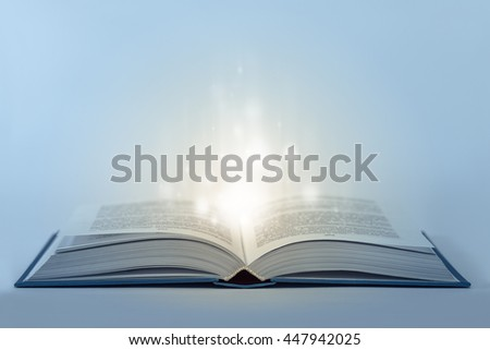 Abstract open magic book on table with light inside. Low aperture shot, focus on front part. Cold and warm tone - stock photo