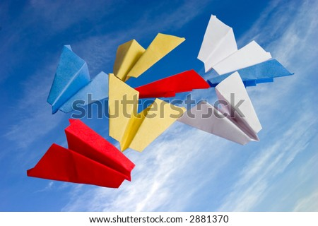 abstract origame paper planes folded from colored sticknotes on cloudy sky background - stock photo