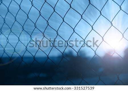 Abstract outside rusty wire fence with beautiful blue colored sun beams and flare. Wire fence barricade closeup background. - stock photo