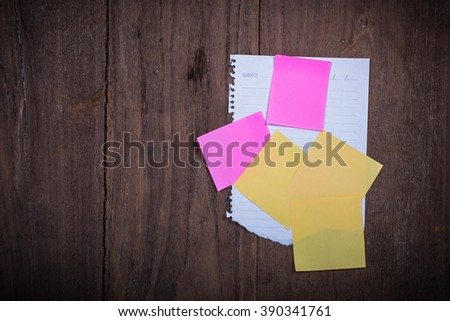 Abstract paper note sticky note pink Yellow  on wood . Background wood with blank notes.  - stock photo