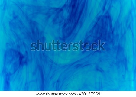 Abstract pattern falling into the water drop of blue ink - cyan ink dissolved in water  - stock photo