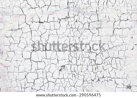 abstract pattern of cracks in old and grungy white washed brick wall - stock photo