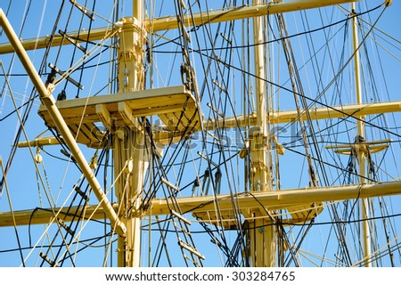 Abstract pattern of sailing ships masts, working platforms and ropes. Yellow details against clear blue sky. - stock photo