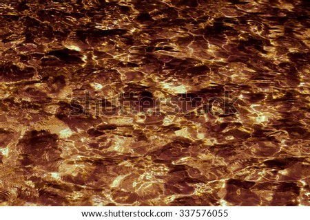 Abstract patterned gold surface water in the pool.