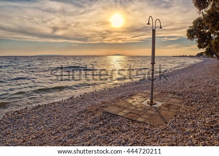 Abstract Pebble Beach Shower at Sunset on Pag Island of Croatia in Artistic Light - stock photo