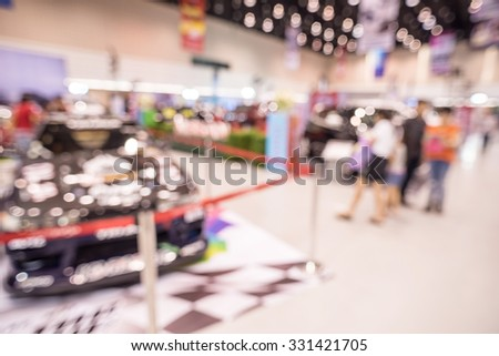 Abstract people walking in motor show, blurred defocusing background. Concept of business social gathering for meeting exchange. - stock photo