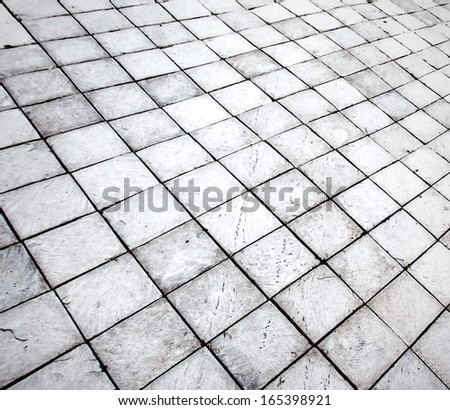 Abstract perspective background of empty textured square and flat light stucco gray and painted white pavement or plaster sidewalk outdoor. An old floor with retro style rows and dark seamless shapes. - stock photo