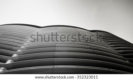 Abstract perspective of a curvaceous concrete structure facade, processed in monochrome. - stock photo