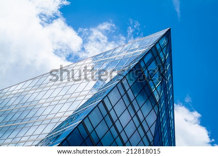 abstract photo of a modern glass building reflecting the sky - stock photo