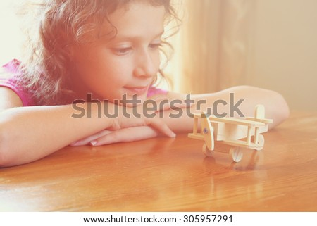 abstract photo of cute kid looking at old wooden plane. selective focus. inspiration and childhood concept  - stock photo