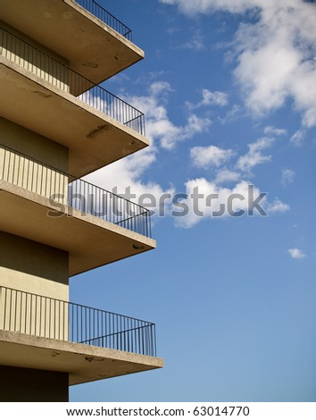 abstract photo of four minimalistic identical balconies against a blue sky. - stock photo