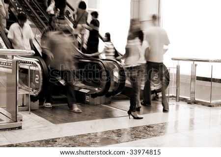 Abstract photo of people moving on escalator in the shopping mall(signs on escalator - bowling, karaoke) - stock photo