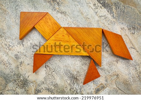 abstract picture of a horse built from seven tangram wooden pieces against slate rock background, a traditional Chinese puzzle game, the artwork copyright by the photographer - stock photo
