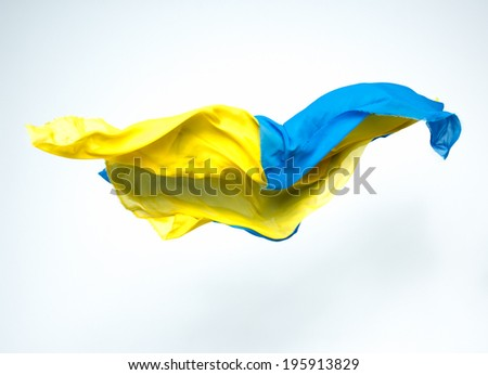abstract pieces of blue and yellow fabric flying, studio shot, design element - stock photo