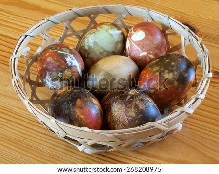 Abstract random color easter eggs in small wooden basket         - stock photo