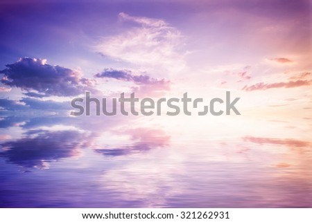 Abstract reflection in water. Reflected purple sky with clouds and sunset - stock photo