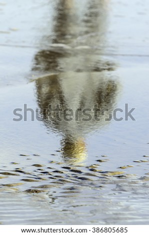 Abstract reflection of unidentifiable fisherman standing in shallow saltwater, with rippled sand above his sunlit head, for themes of illusion, alternate reality, mystery (selective focus) - stock photo