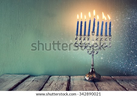 abstract retro filtered low key image of jewish holiday Hanukkah with menorah (traditional Candelabra). with glitter overlay  - stock photo