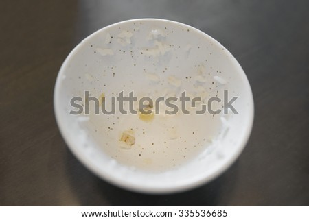 Abstract shallow DOF of empty bowl of japanese rice over dark table - stock photo