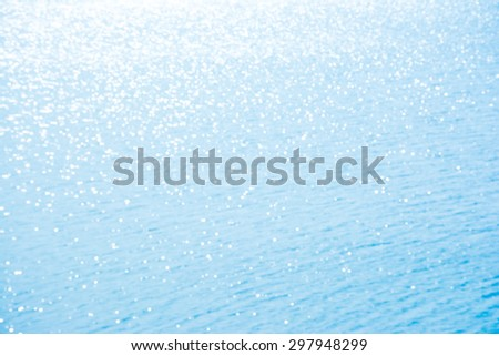 Abstract shining sunlight bokeh on blue sea water background. - stock photo