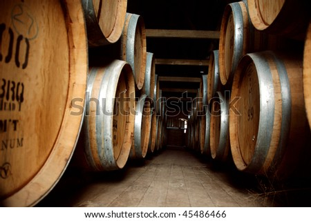 Abstract shot of aged wine barrels in wine cellar at winery - stock photo