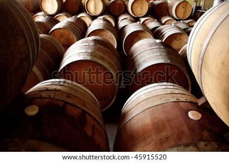 Abstract shot of rows of old wine barrels in storage at winery cellar - stock photo