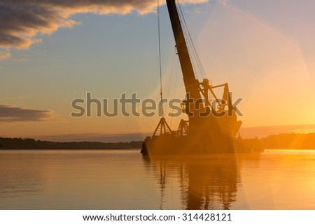 Abstract silhouette of a floating crane at sunrise. - stock photo