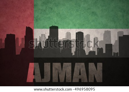abstract silhouette of the city with text Ajman at the vintage united arab emirates flag background