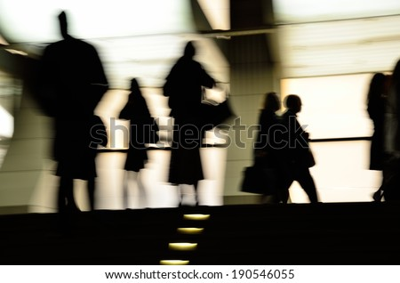 Abstract silhouettes of people in motion blur on bright background