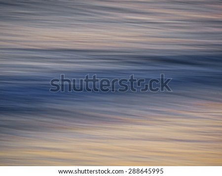 Abstract slow movement of the surf toward the beach at sunset. - stock photo