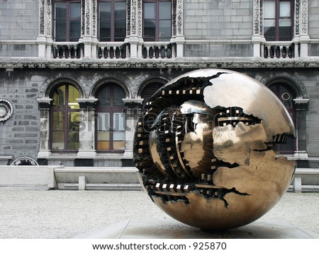 Abstract, spherical metal sculpture on a courtyard of Trinity College in Dublin, Ireland. - stock photo