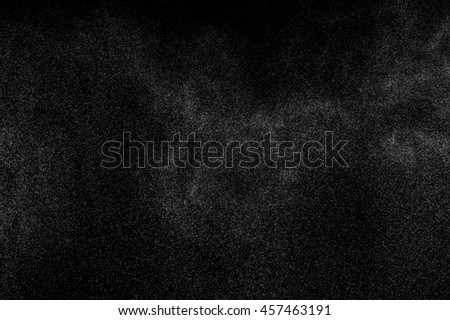 Abstract splashes of water on black background. Freeze motion of white particles. Rain, snow texture. - stock photo