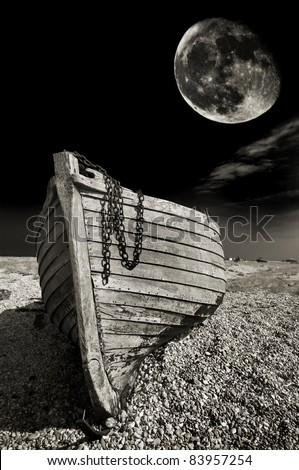 abstract, spooky, warm toned black and white image of an abandoned wooden fishing boat on the beach at Dungeness, UK, with a harvest moon in the background - stock photo