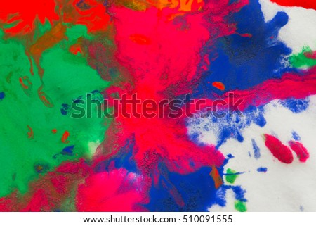 abstract spots splash of bright red, green, blue colors on white paper macro