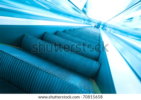 abstract steps of vanishing escalator with persons on the top - stock photo