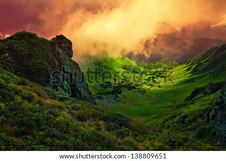 abstract stone giant and orange fog over the green Carpathian mountain valley - stock photo