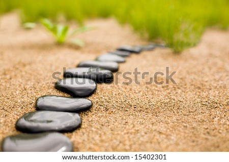 Abstract stone path on sand on a background of a grass - stock photo