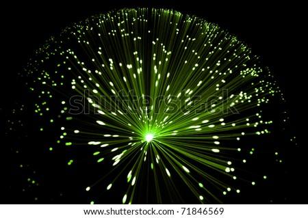 Abstract style overhead view of illuminated fiber optic strands against black. - stock photo