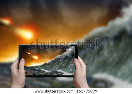 Abstract tablet pc in hands photographs giant tsunami waves crashing small coastal town and asteroid impact