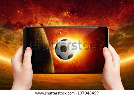 Abstract tablet pc in hands, soccer ball on screen, multimedia gadget, soccer, football game. Elements of this image furnished by NASA/JPL-Caltech