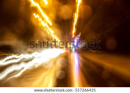 Abstract traffic with color lights in the dark. Blurred car and road.