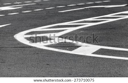 Abstract transportation background. White bent lines over dark gray asphalt, road marking. Selective focus with shallow DOF