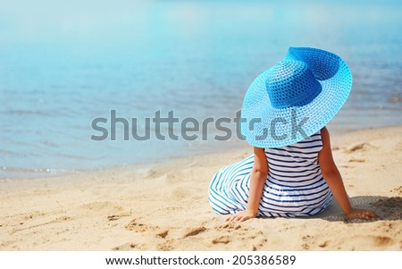 Abstract travel photo pretty little girl in dress and hat enjoying on the beach near sea
