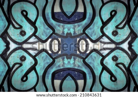 Abstract tribal design. Close up of graffiti elements reflected to create a pattern. - stock photo